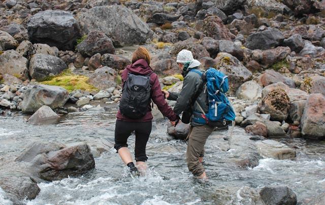 Her får togturistene prøvd seg som fotturister, og det nytter ikke å være redd for å bli våt på bena. Vi kommer oss helskinnet, men ikke tørrskodd over en elv i Tongariro nasjonalpark.