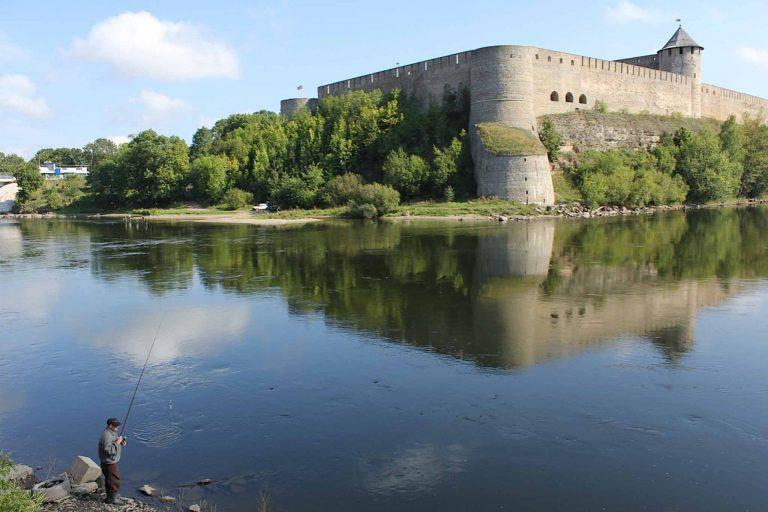 En fisker på estisk side av elven har utsikt over til Ivangorod-festningen på russisk side.