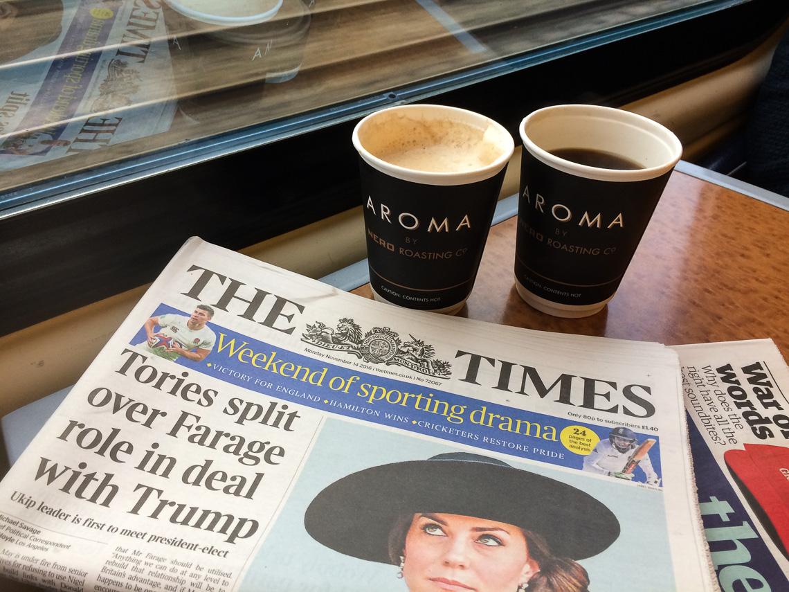 Vi har aviser og kaffe og er om bord på toget fra London til Holyhead.