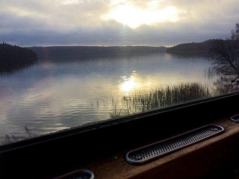 Utsikt fra et vindu i retrotoget til en speilblank svensk innsjø.