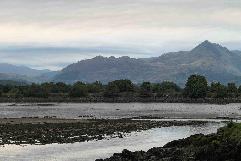 Porthmadog i Wales: Men se - der zoomer kameraet inn på raggete fjelltopper i lett morgendis.