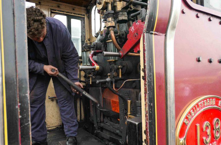 Frivillige spar kull og får opp dampen på Ffestiniog Railway, Wales.