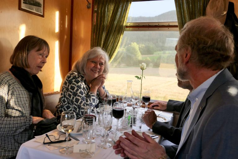 Gode venner hygger seg med 4 retters middag om bord i et museumstog fra Historiske togreiser.