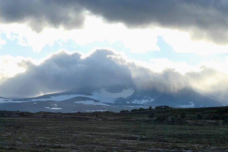 Snøhetta, 2286 moh, leker gjemsel på dette bildet, men bak skyene er dette Norges høyeste fjell utenfor Jotunheimen. (Foto tatt på tilbaketuren, i litt annet vær enn de andre bildene.)